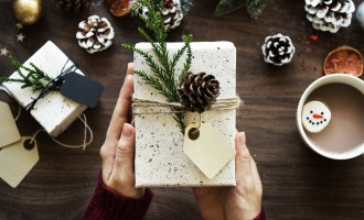 Two hands holding alight coloured present with a fir cone on it and around it. Fantastic Christmas Gift Ideas for Your Mum