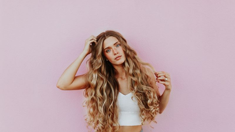 Girl with gorgeous blonde curls near a pink wall