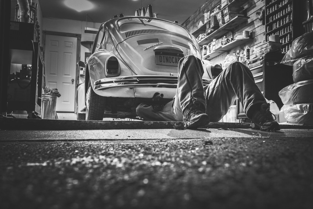 Car servicing and Maintenance for Your Family Car Black and white photo of man under old VW Beetle car doing some repairs