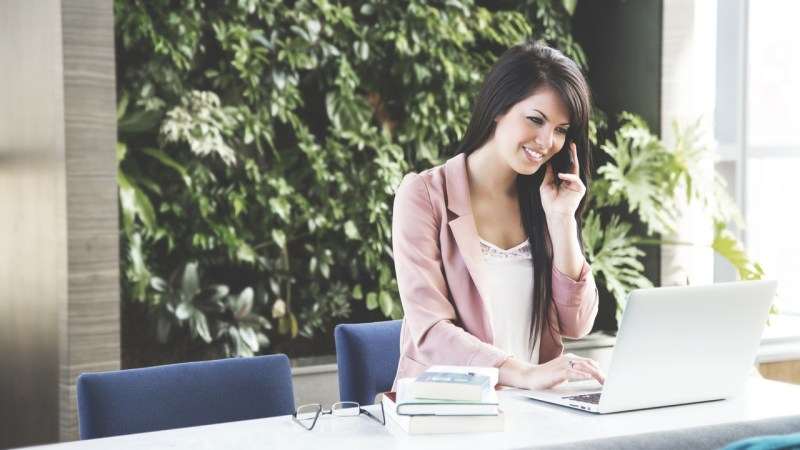 Flying Solo - Tips to Succeed as a Female Entrepreneur. Woman in light pink jacket on the phone
