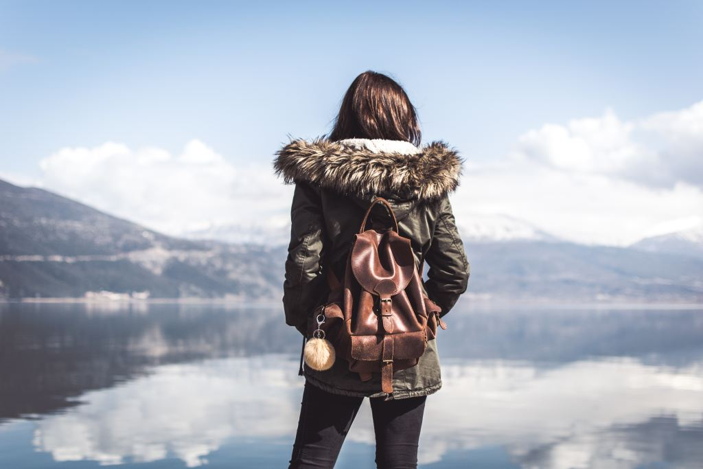 brown packpack on the back of a girl looking out over a lake