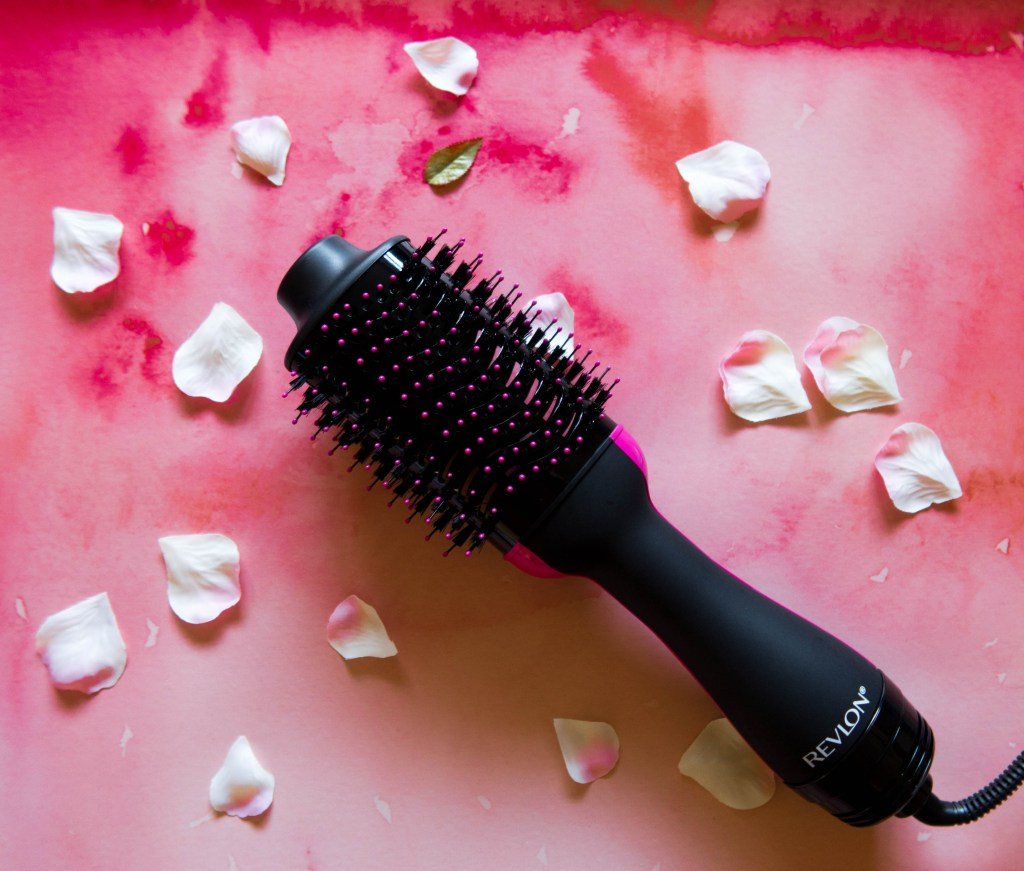 One Step Volumizer review - picture of hotbrush on a hot pink backgrounf wtith scattered flower petals