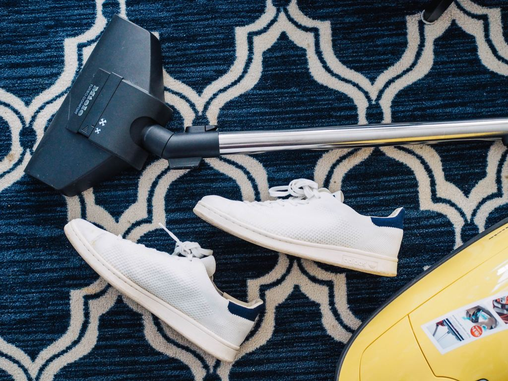 vacuum and shoes on a patterned blue carpet