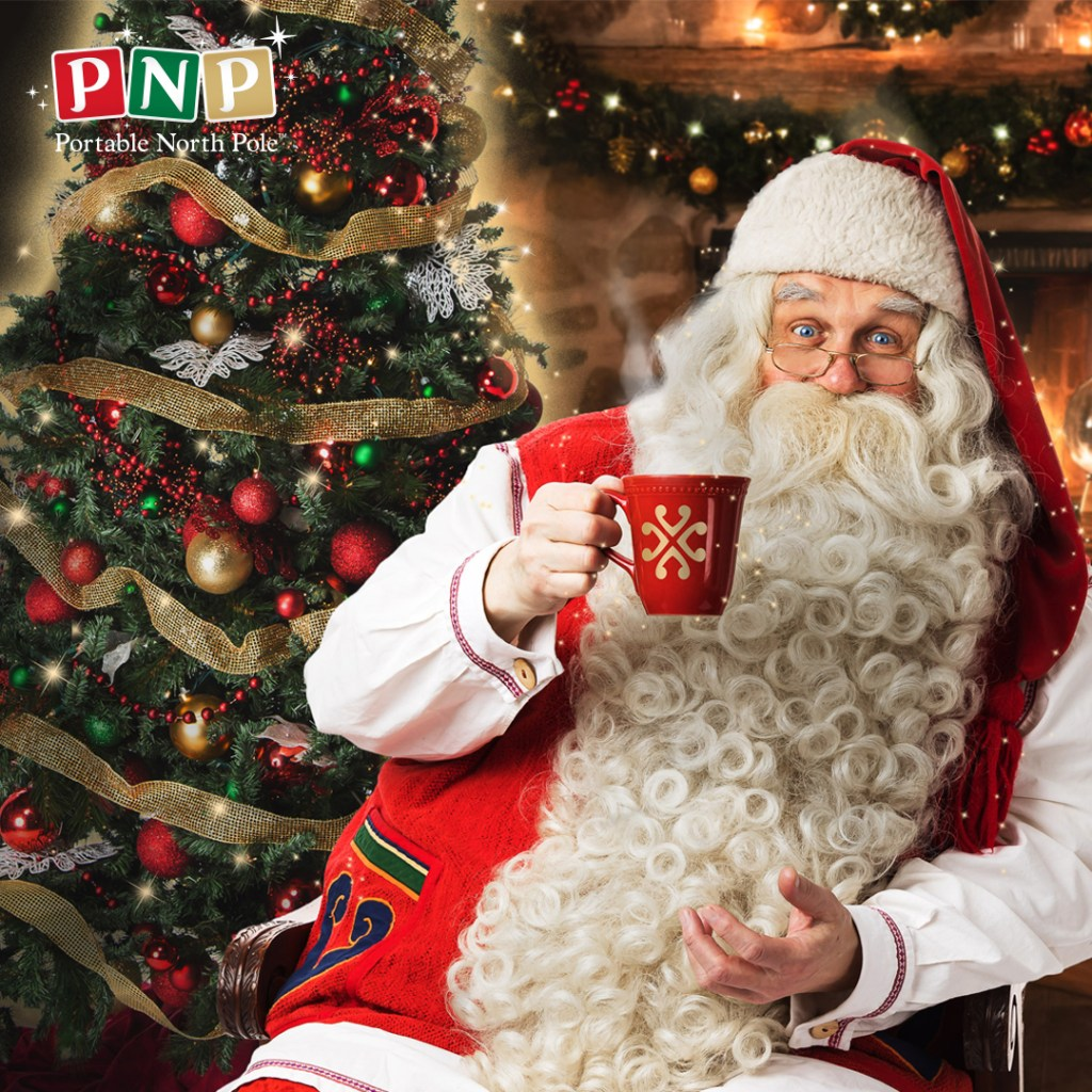 PNP Santa, sat near a decorated Christmas tree, with the glow of a fire behind him, holding a red mug that I'd like to think is full of Advocaat, but probably it's just a cuppa!
