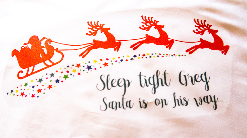 "pillowcase has Santa on a sleigh being pulled by reindeer, text reads ""Sleep tight Greg Santa is on his way"""
