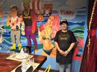 The cook posing in from of the mural she painted.