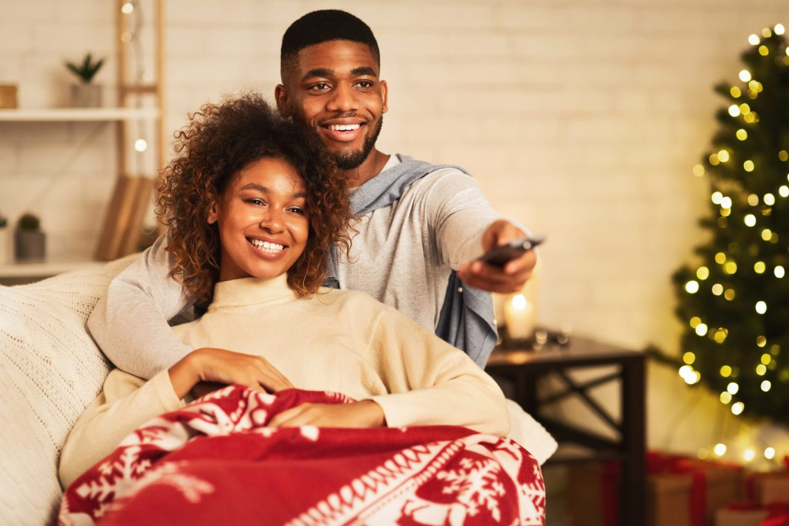 Afro couple in love at Christmas eve enjoy watching tv, lying under plaid on sofa