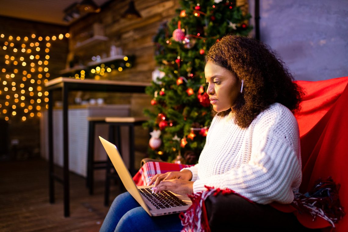 afro woman shopping online on laptop in cozy christmas interior.Preparing to xmas, lying on winter sales.