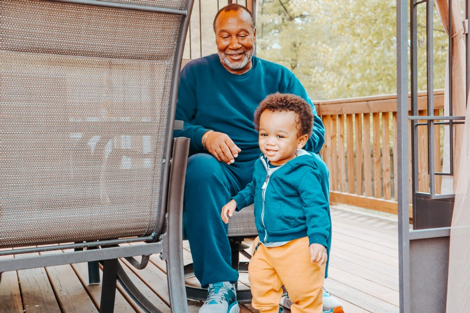 grand father and grand son playing in the backyard