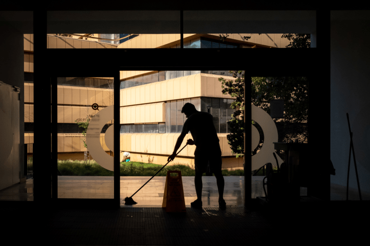 Man mopping the floor of an office building