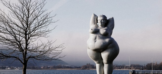 statue of a fat woman by a lake