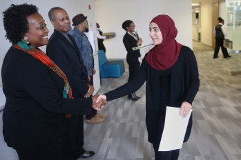 Linda Wright Moore, widow of Acel Moore, left, shakes hands with Zuha Mutan during the Acel Moore High School Journalism Workshop awards luncheon at the Philadelphia Media Network office in Center City on Saturday, April 7, 2018. The luncheon honored the 21 students who participated in this year's workshop. TIM TAI / Staff Photographer