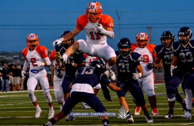 Senior Running back #11 Aaron Moya hurdles over Del Valle's #13 Jose Valenzuela during the Canutillo Eagles at Del Valle Conquistadores in a district 2-5A showdown at Conquest Stadium