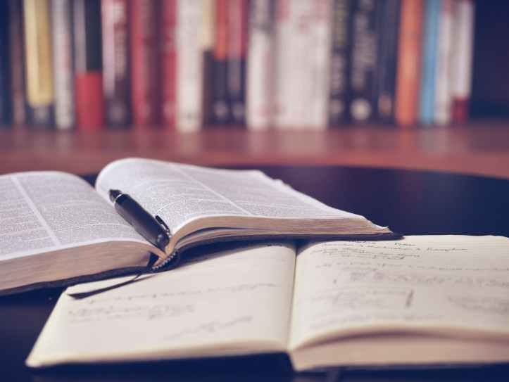 Pen and open notebook and reference book; a library shelf in the background.