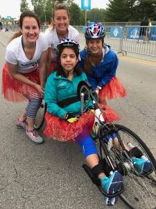 in picture is Guide Lauren Kollinger, Guide Amanda Hachey, Guide Susie Bousquet, and Sara Solomon in the handcycle at Geist Half Marathon