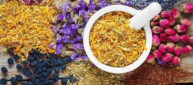 Mortar of dry marigold flowers, healthy herbs, herbal tea assort