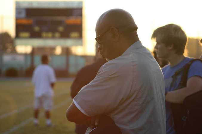Heads bowed during a moment of silence held for two would-be seniors on Friday's football game against Palo Altos.