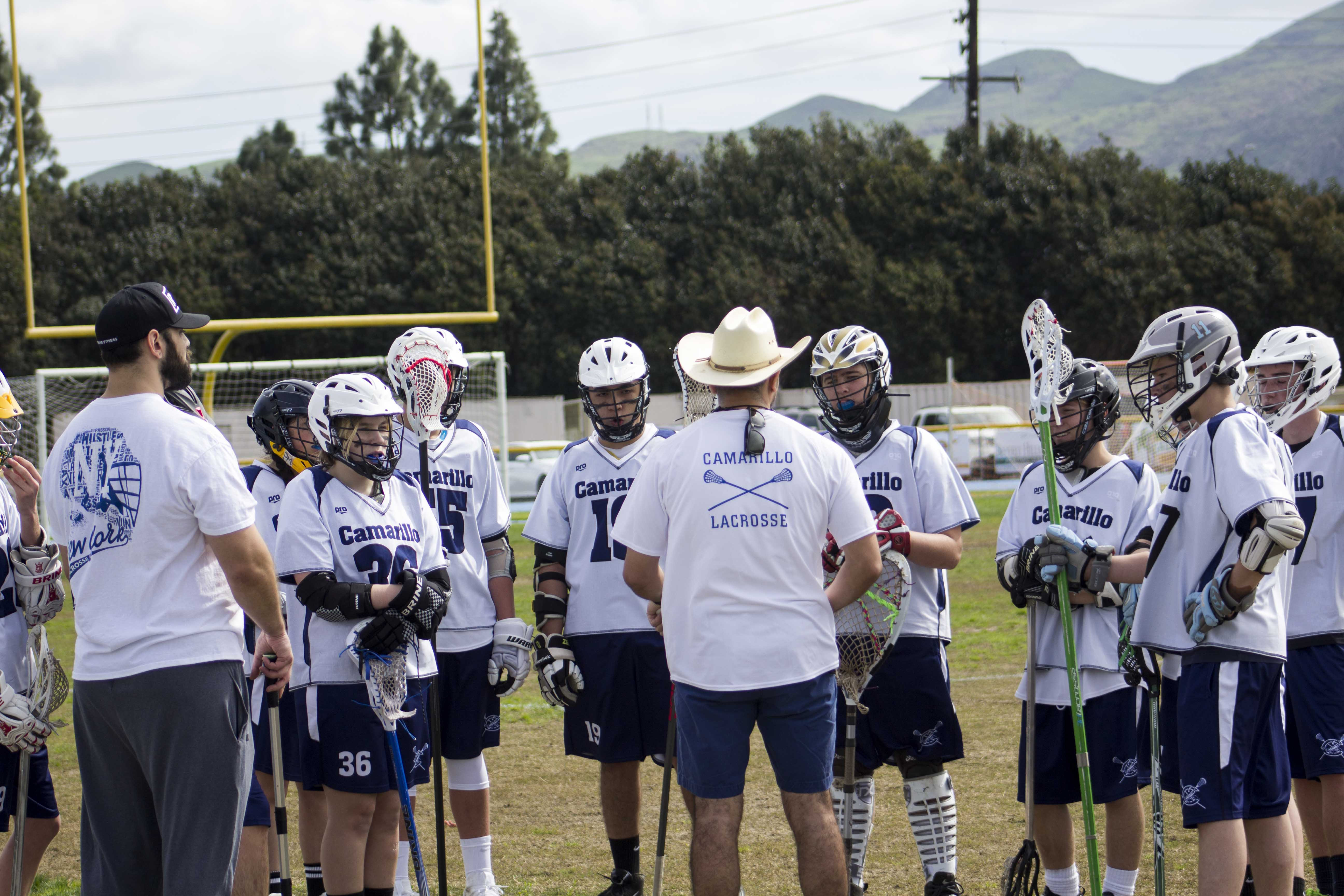 The team discussing game strategies during halftime with the coach, Andrew Morales.