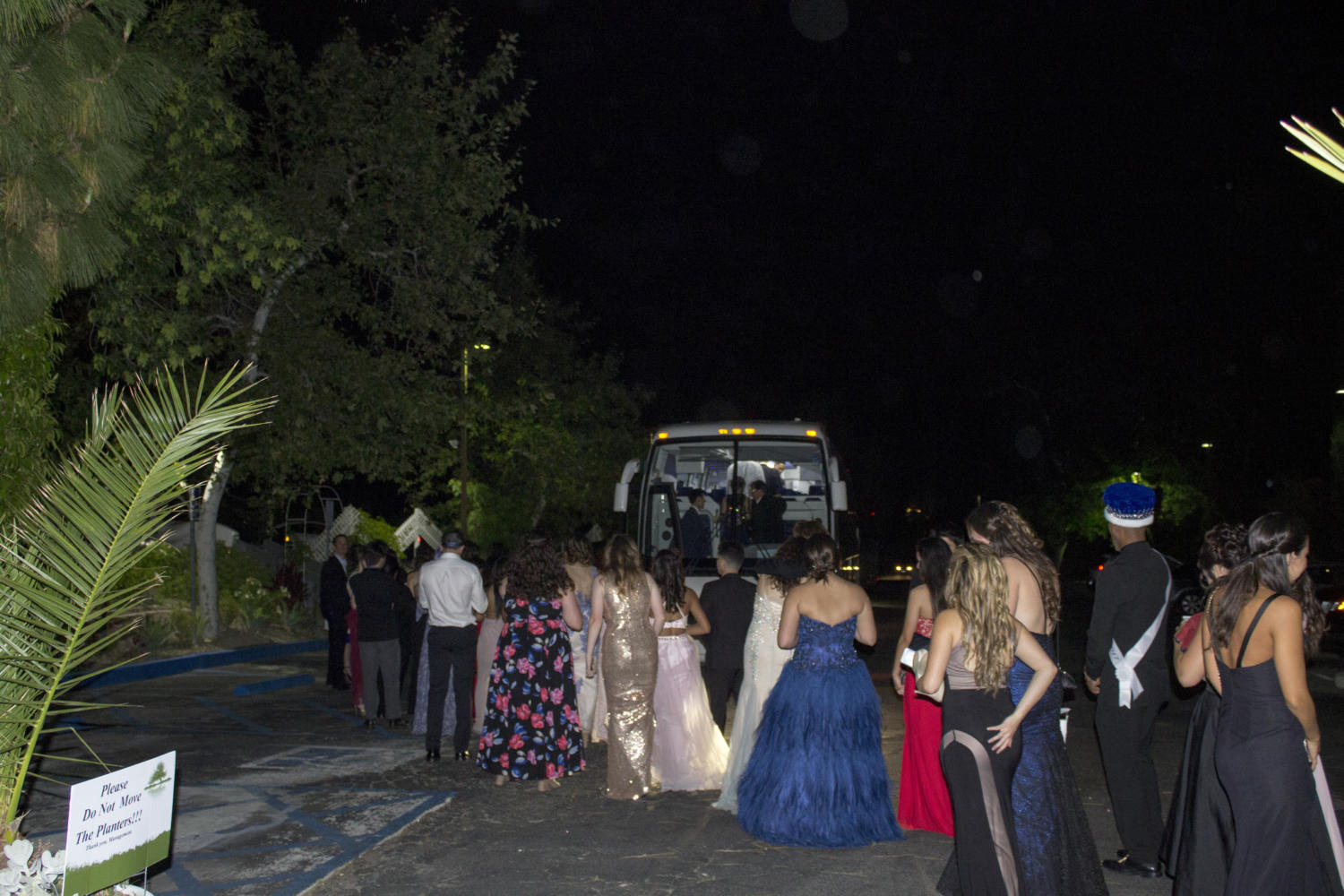 Students wait in line to depart on charter buses towards the end of Prom.