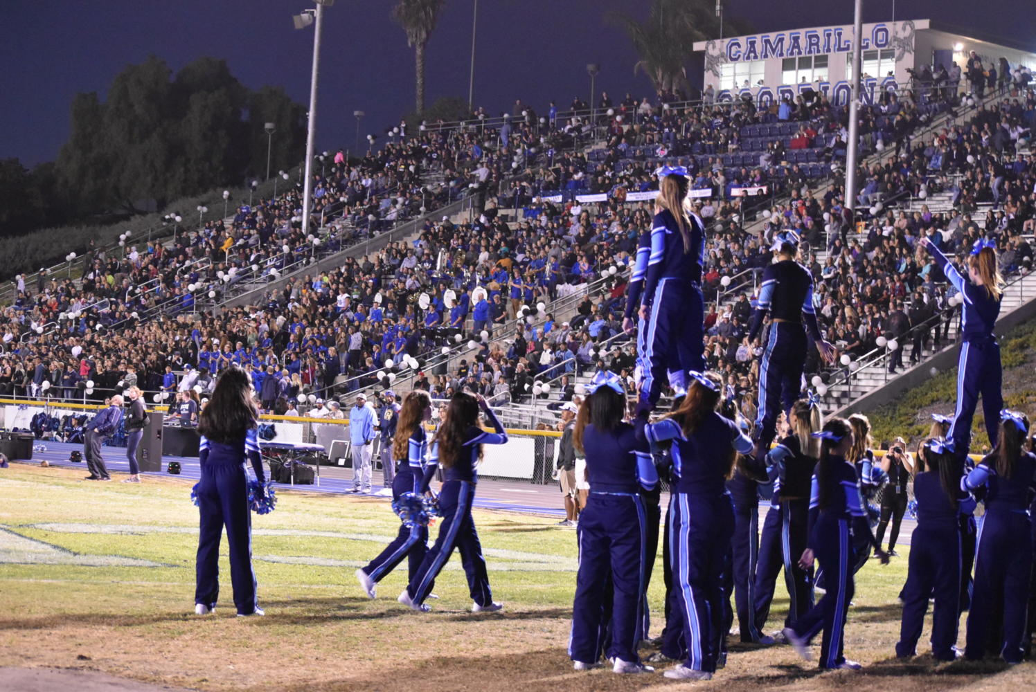 Cam High's cheer team stands proudly at the edge of the endzone to celebrate a touchdown.