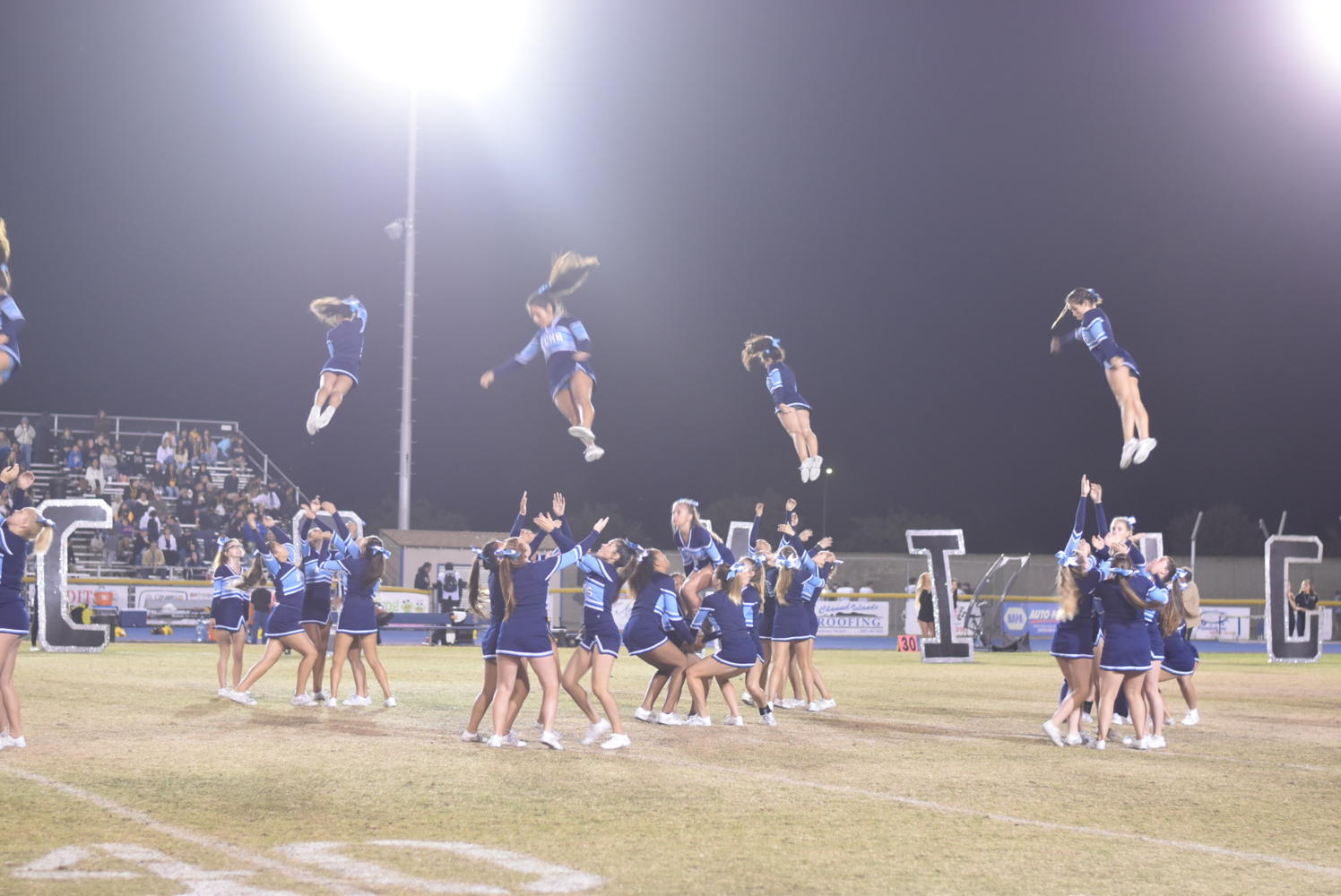 The varsity cheer team performs during half-time.