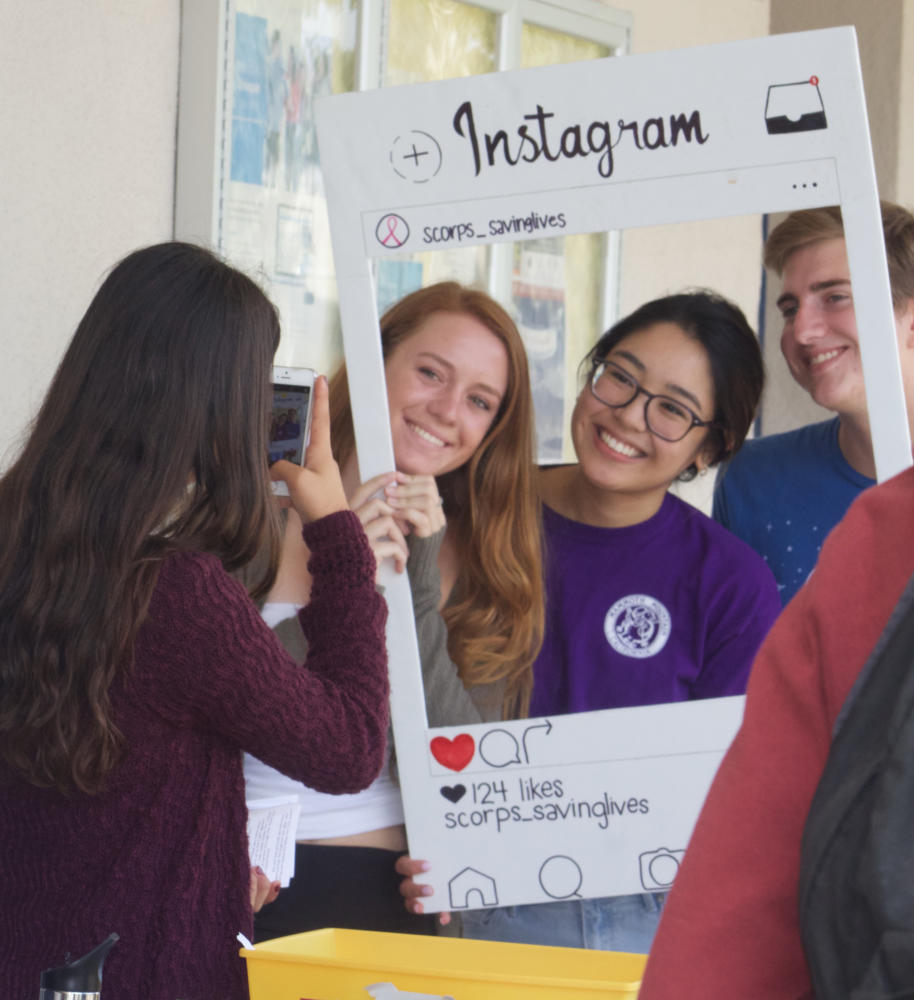 Seniors (from left to right) Kellie Farrell, Abby DeLaMerced, and Chris Keating pose with the American Cancer Society Instagram cut-out to promote the club on social media.