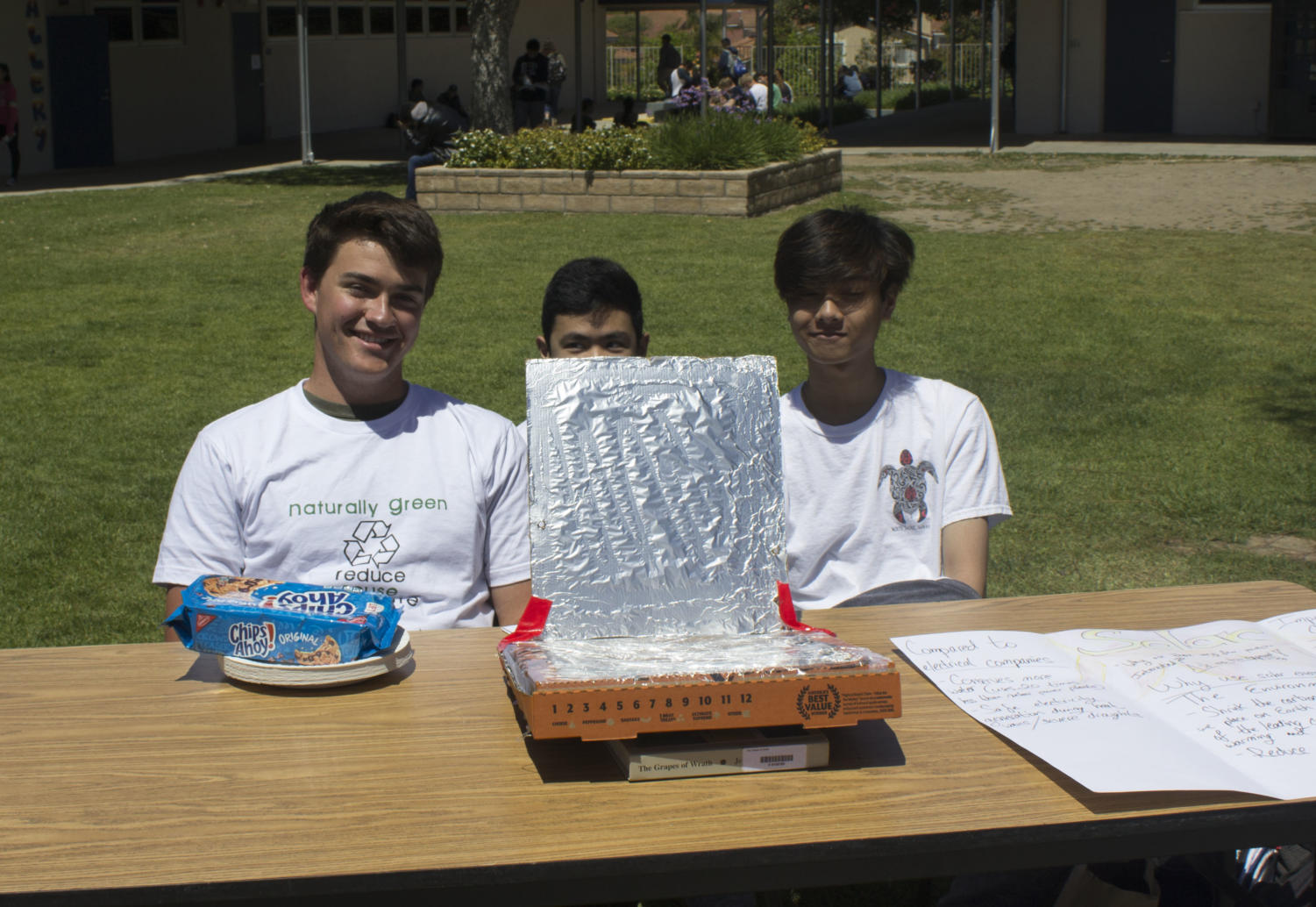 Photo By : Catherine Wolfe (from left to right) Kellen Barsley Junior, Jonathan Lao Junior , and Jon Puno Junior presenting a pizza box microwave at naturally green celebration.