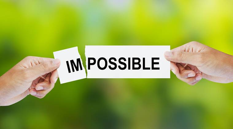 Businessman tearing the word Impossible for Possible
