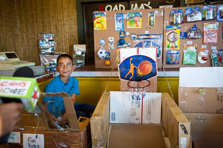 A photo of Caine and his homemade cardboard arcade