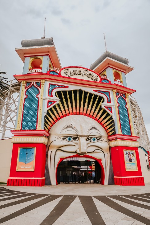 Photo of the facade of Luna Park in Melbourne Australia. The facade has the face of a clown with red lips and blue eyes and a crown of spikes in red, yellow and orange. The pillars either side are adorned with blues, reds and yellow. Luna Park in St. Kilda is an iconic landmark that makes for an awesome Instagram spot.