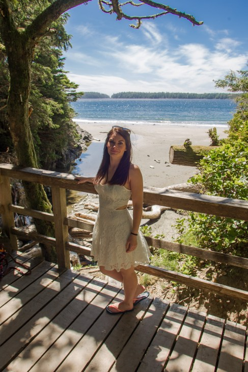 The boardwalk trail to Tonquin Beach Tofino - Photo of a girl standing on a wooden boardwalk surrounded by green trees with an opening revealing a beach with blue ocean water