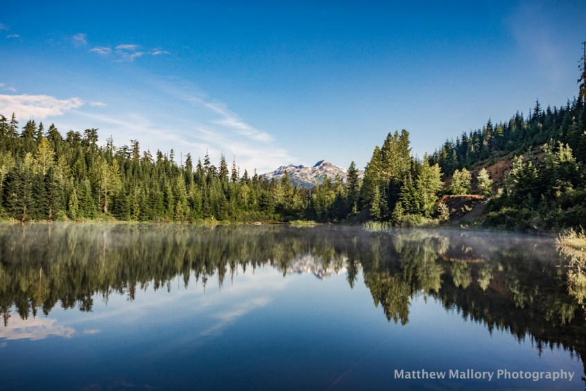 Photo of a lake with a flat reflection of the blue sky and green trees with a mountain peak in the background.