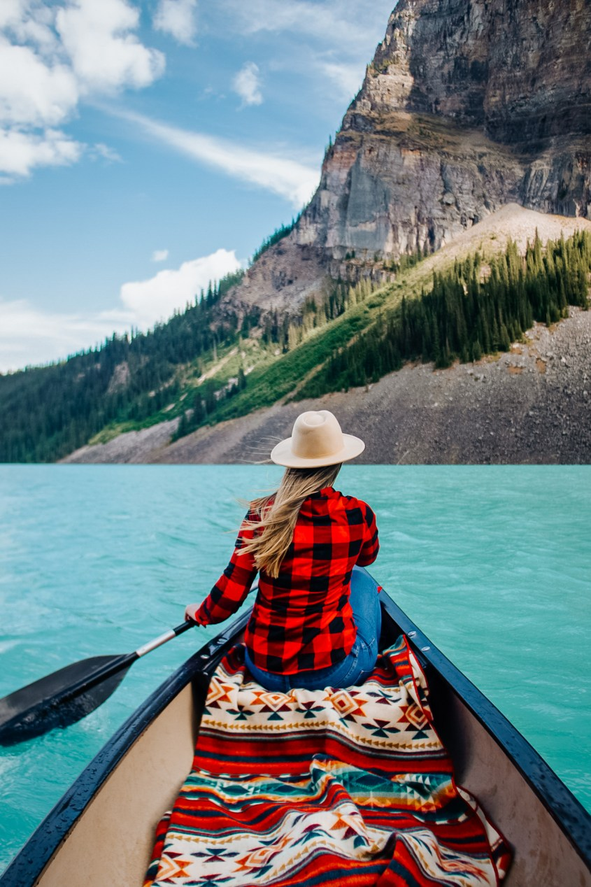 Photo of a woman sitting in a canoe on a turquoise blue lake, facing forward towards mountain peaks. She is wearing a fedora hat, plaid red shirt and blue jeans and sitting on a multicoloured blanket.  Canoeing on Lake Louise, Alberta.
