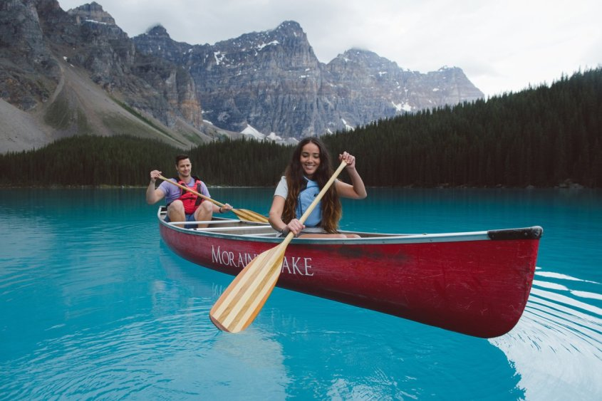 Photos of a man and a woman sitting in a red canoe on a bright blue lake with snow-capped mountains in the background. Canoeing on Moraine Lake