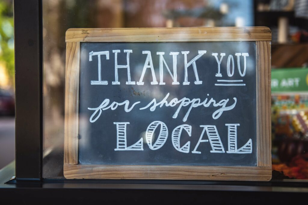 """Chalkboard sign in a window that says """"Thank you for shopping local"""""""