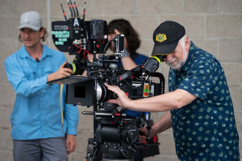 Cinematographer Henry Pierce ACS behind viewfinder, with first assistant camera Pim Kulk in the background, on location with 'Between Two Worlds' - PHOTO Brook Rushton
