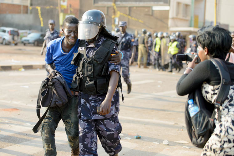 A rare image of a man being helped by a policeman after being shot with a teargas cannister during a demonstration in Wandegeya. Police had blocked Kizza Besigye from accessing Makerere University where he was meant to hold a campaign rally, hence the rioting supporters. Photo first published on twitter. Taken in Wandegeya