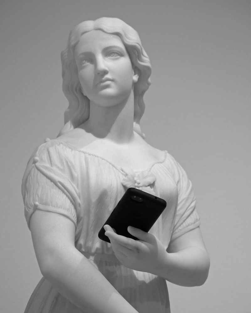 old statue of young woman with smartphone in museum