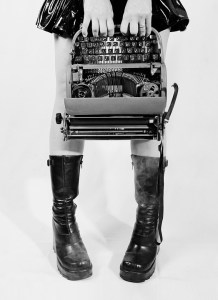 girl in goth boots holding typewriter