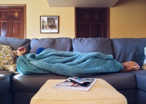 Man under blanket on couch