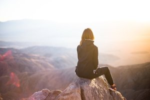 Woman sitting precariously on the top of a mountain.