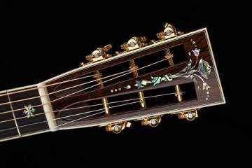 closeup of a vintage acoustic guitar's slotted headstock and tuners