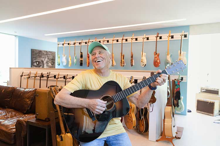 Jimmy Buffett smiling while playing a Martin acoustic guitar in his home