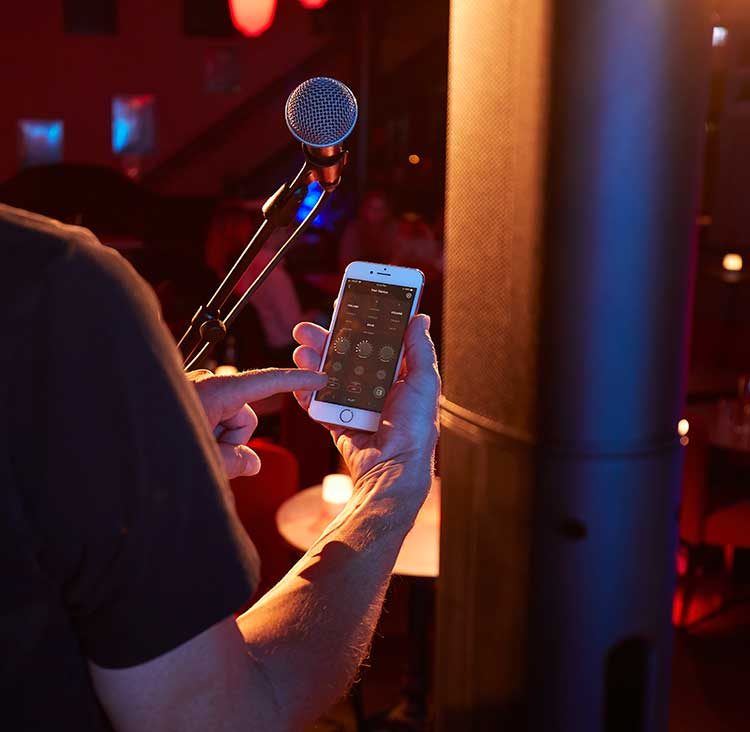 musician holding smartphone using Bose mix app onstage