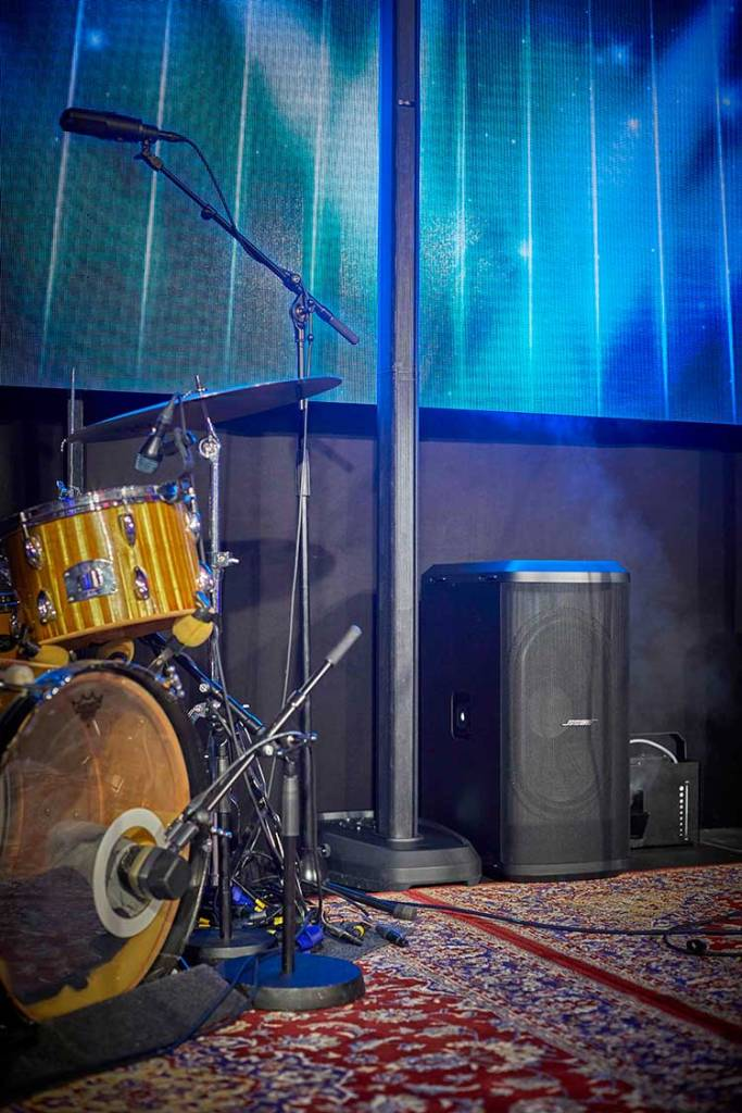 bose l1 personal pa system onstage behind a drum kit