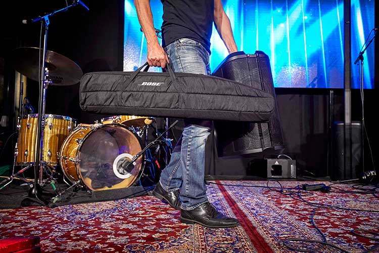 musician carrying bose l1 personal pa system in carry bag onstage