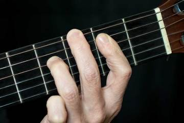 close up photograph showing three fingers on a guitar neck playing a Gmaj9 chord