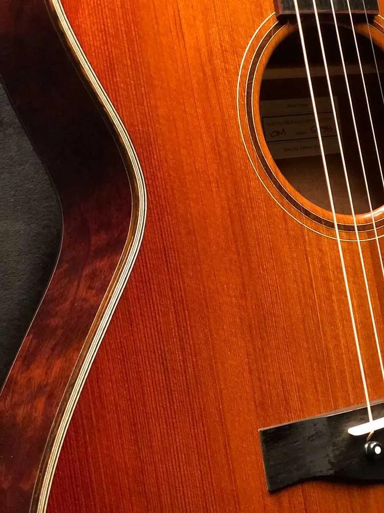 Closeup of binding, soundhole, and bridge of a 2021 Santa Cruz OM Custom acoustic guitar made from Tunnel 13 Redwood