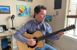 Sean McGowan holding acoustic guitar in his home studio