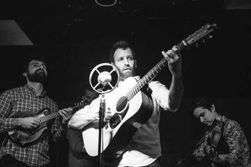 Alan Barnosky playing acoustic guitar in front of an old style microphone